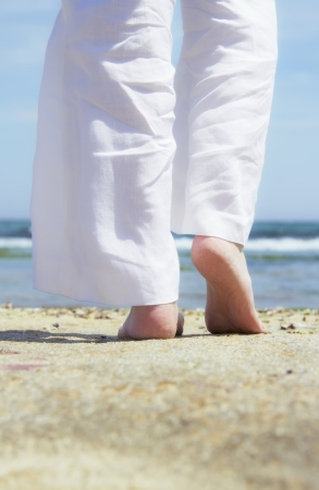women s feet: A young woman walking on the sand  Stock Photo