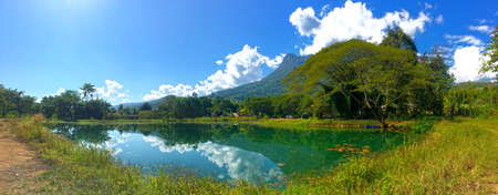 Mountain Doi Luang Chiang Dao reflecting in a lake surrounded by trees and white clouds on blue sky. Beautiful summer scenery in Thailand. Фото со стока