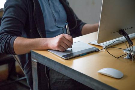 artistas: Hombre que usa el l�piz y la tableta para el trabajo Foto de archivo