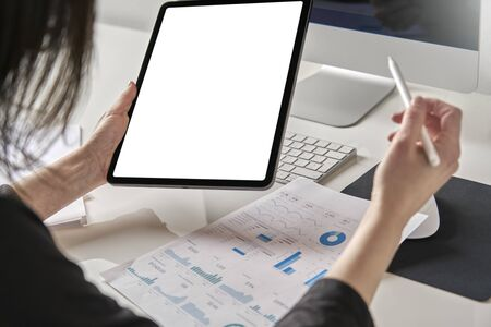 A businesswoman consults marketing statistics and analyzes the company's growth online with her tablet