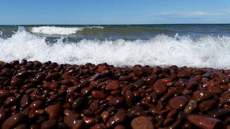 waves crashing: Dark red rock beach with waves crashing Stock Photo