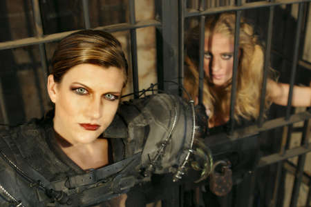 Close up of a futuristic female guard with her female prisoner looking on.