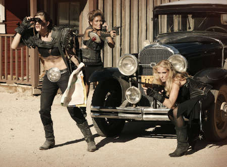 Three tough women engage in a shootout over a vintage car. photo