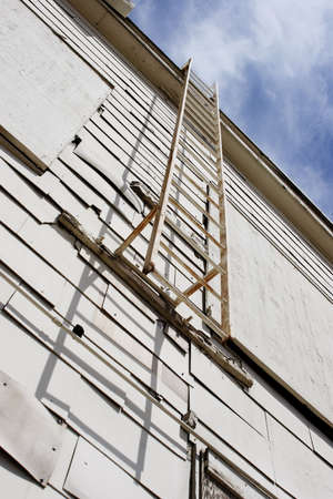 Emergency ladder from the roof of an abandoned white airport hangar.