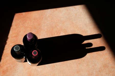 重い側光と長い、劇的な影とワイン bottels