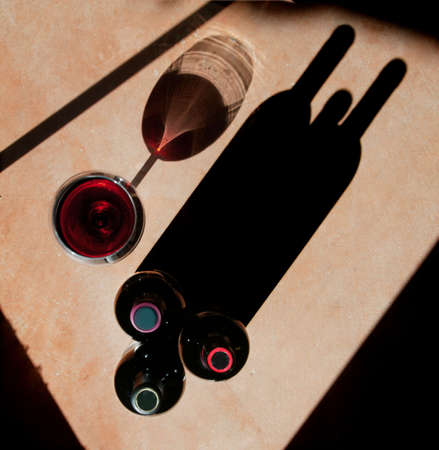 pinot: Wine bottels and wine glass with heavy side-light and long, dramatic shadow.  Stock Photo