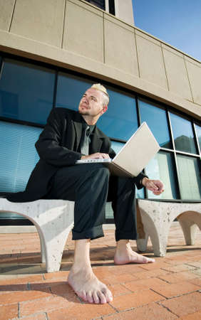 Barefoot businessman with a punk haircut works on his laptop computer on a bench in a business park. photo