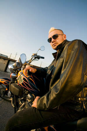 Man with a punk haircut in a leather jacket sitting on his motorcycle. photo