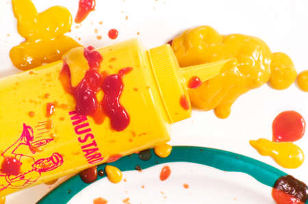 woman squirt: Mustard squeeze bottle and a mess of condiments on a plate.