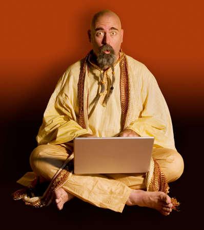 illuminati: Guru divertente che si siede con un calcolatore di laptop. Archivio Fotografico