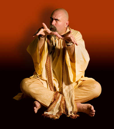 Funny guru sitting lotus style casts an evil spell. Stock Photo - 1525928