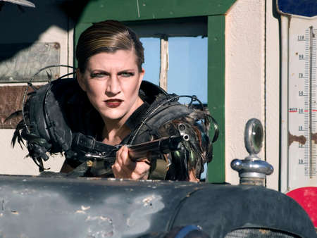 anachronistic: Science fiction woman hides with a rifle behind a vintage car.
