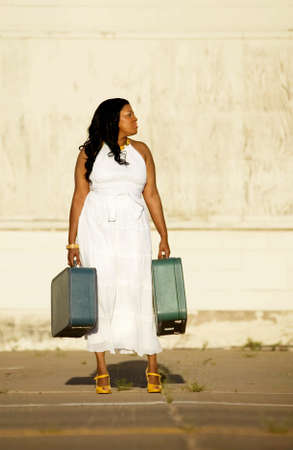 arrive: African American woman with suitcases waiting by the street for someone to arrive.