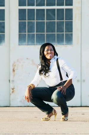 medium shot: Medium shot of an African American woman at an airplane hangar.