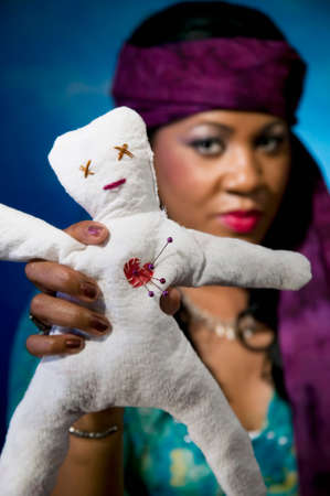 Gypsy fortune teller with an unfortunate voodoo doll. Stock Photo
