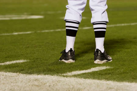 sideline: Referres feet on a football field from behind.