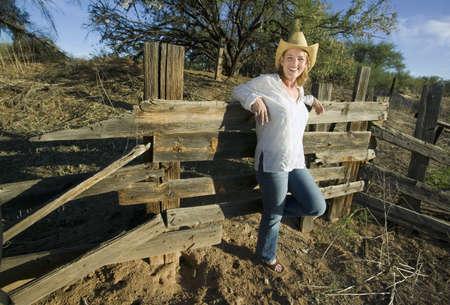 decrepit: Western woman leans against a decrepit old split rail fence. Stock Photo