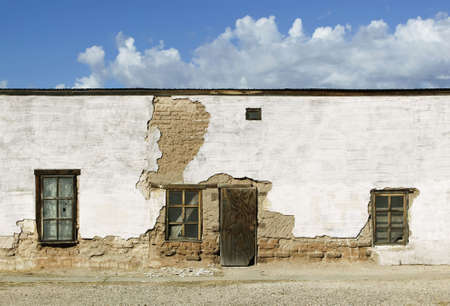 Boarded and abandoned adobe building with a door and windows. photo