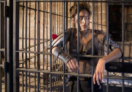 Tough science-fiction woman behind bars in a retro jail. Stock Photo