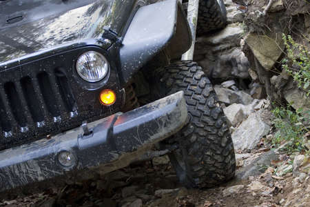 grille: Headlight and grille on a four-wheel drive vehicle traveling over rocks. Stock Photo