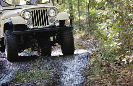 grille: Headlights and grille on a vintage four-wheel drive vehicle driving in the mud.