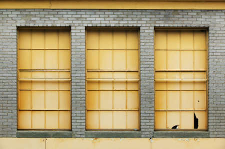 symetry: Three yellow windows on an industrial brick building.