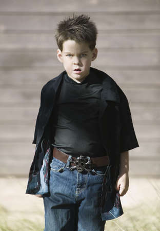 defiant: Young boy with a defiant attitude wearing a black shirt and a pirate belt buckle. Stock Photo