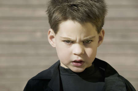 defiant: Close-up of a young boy with a defiant attitude.
