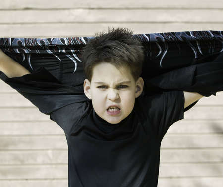 misbehave: Young boy with his shirt stretched behind his head and a scary look on his face. Stock Photo
