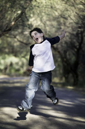 airborn: Young boy on a tree-lined path jumps in the air.