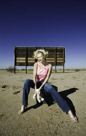 Woman sitting on suitcases in front of an old billboard waiting in the desert. photo