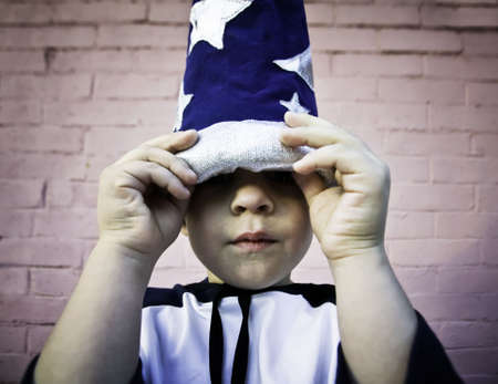 wizard hat: Young boy lifts the brim of a wizard hat and peers out.