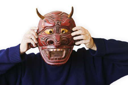 person wearing a blue sweater holding up a red devil mask photo