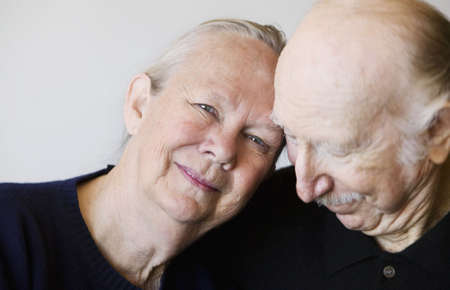 Close-up of senior couple embracing focuses on smiling woman
