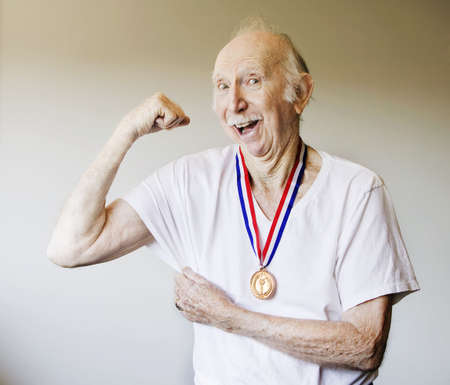 Senior Citizen Posing with a Gold Medal