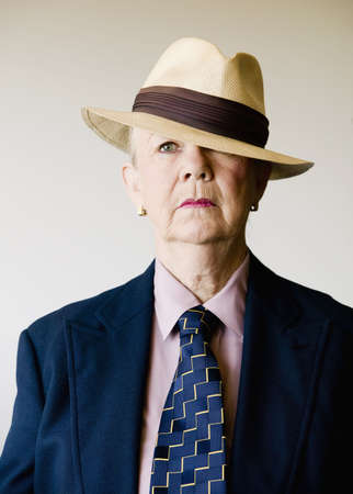 Dramatic senior woman in a man's suit wearing a straw gangster hat