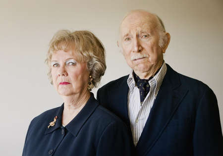 cowering: Portrait of Wealthy and Snooty Senior Citizens with Strong Woman and Cowering Man Stock Photo