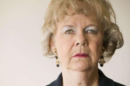 disdain: Close-up of a senior woman looking directly at the camera.