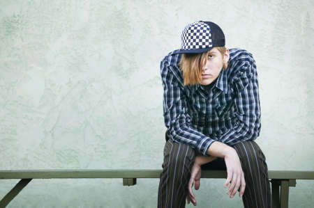 mismatch: Teenage boy with crazy hair and a clothes on a green bench.