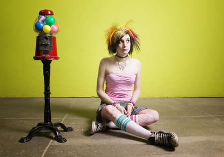 Colorful young punk girl sitting in front of a green wall photo