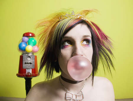 Punk Girl in front of a Green Wall Blowing a Bubble photo
