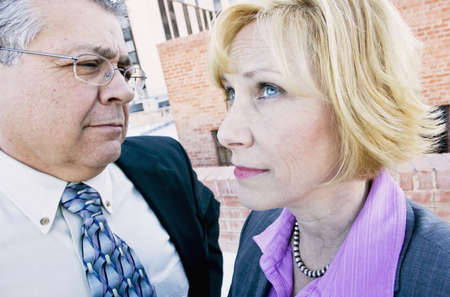 quizzical: Executive man and woman on a downtown roof with ambiguous expressions