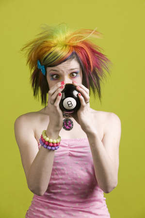 Close-up of a woman with bright mascara and colorful hair predicts the future photo