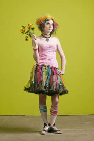 Pretty young woman with colorful punk clothes with plastic flowers. photo
