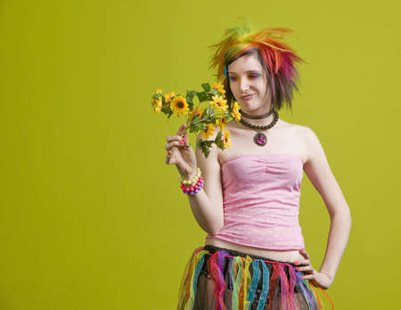 Pretty young woman with colorful punk clothes considers plastic flowers. photo