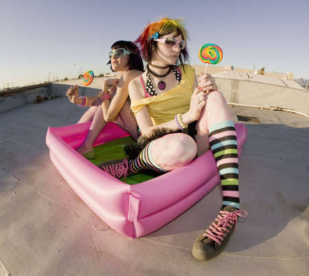 blowup: Fisheye shot of girls in brightly colored clothing in a plastic pool on a roof with sunglasses and lollipops