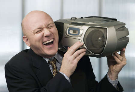 Bald businessman listening to a boom box Stock Photo