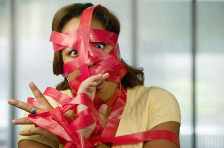Businesswoman wrapped in red tape Stock Photo