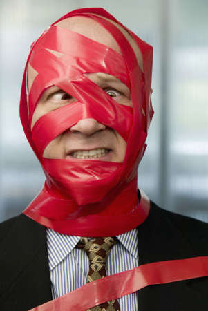 impediment: Cross-eyed businessman wrapped in red tape