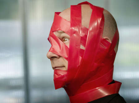 Businessman wrapped in red tape Фото со стока